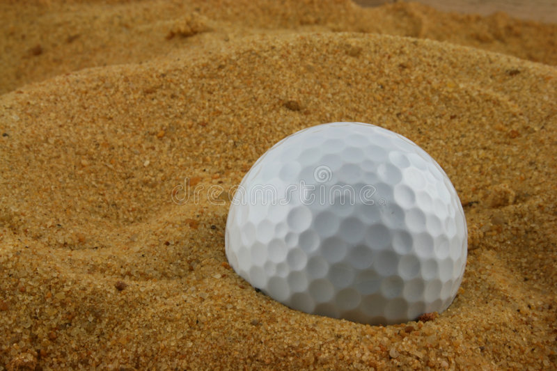 Golf Ball in the Samd. Golf Ball buried in the Sand royalty free stock photos