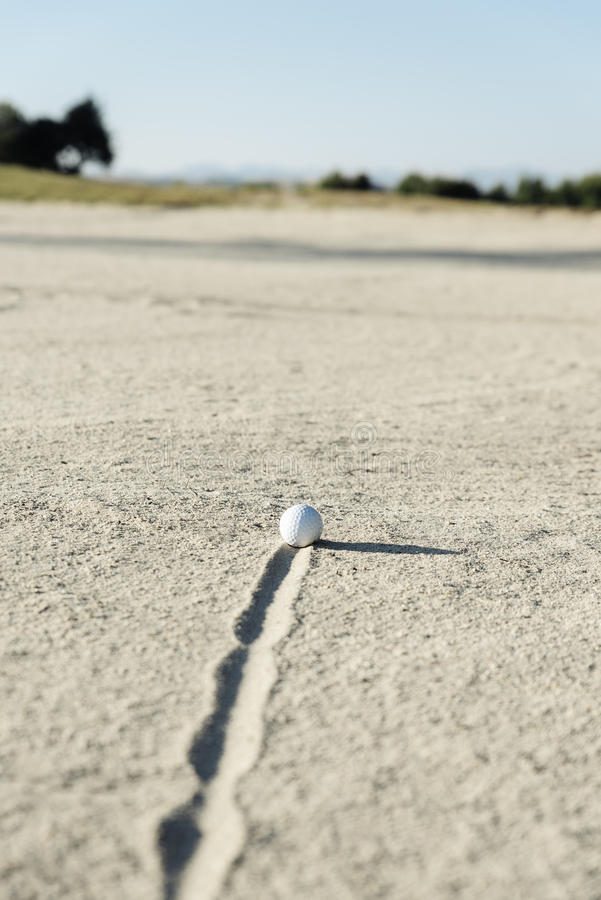 Golf ball in sand bunker stock photo