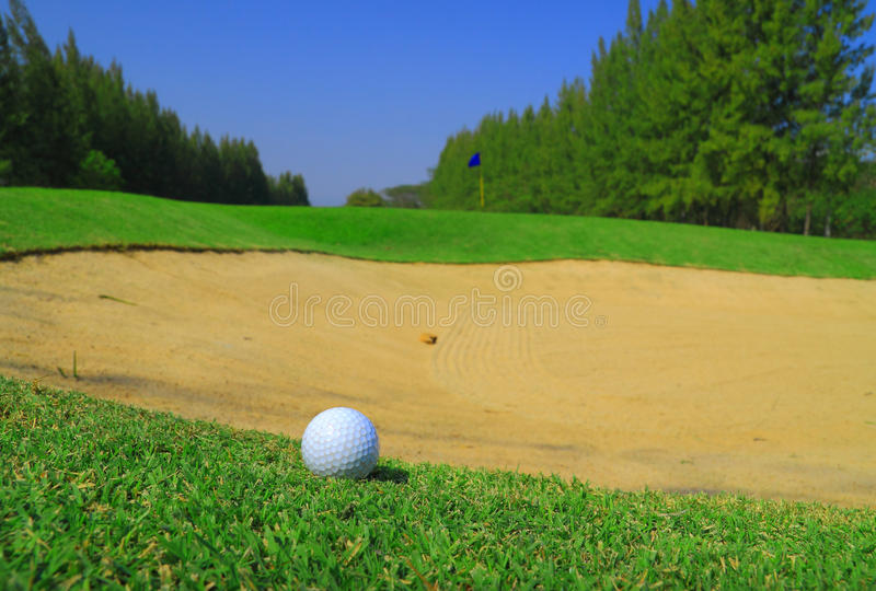 Golf ball and sand hole. Golf ball on green grass and sand hole stock image