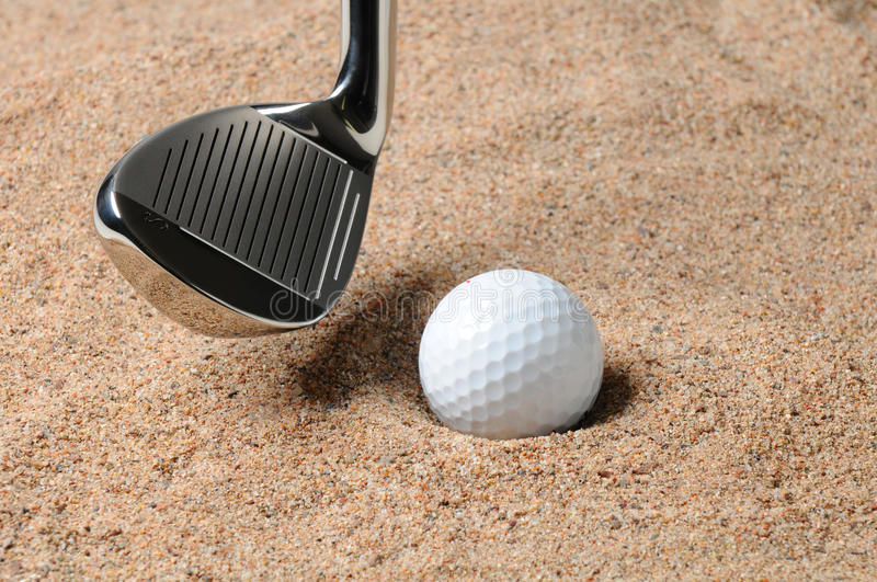 Golf Ball in Sand Trap. Golf Ball in Trap with Sand Wedge about to strike the Golfball. Close up in horizontal composition with copy space stock photos