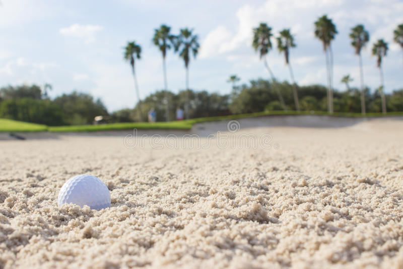 Golf Ball in Sand Trap. A golf ball in the sand trap of a beautiful golf course stock image
