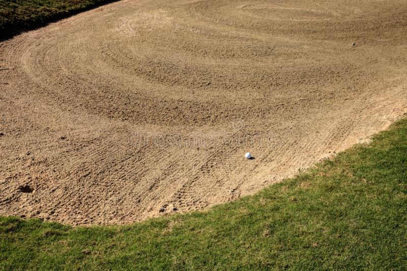 Golf ball and a sand trap. On Lush green grass on a golf course stock images