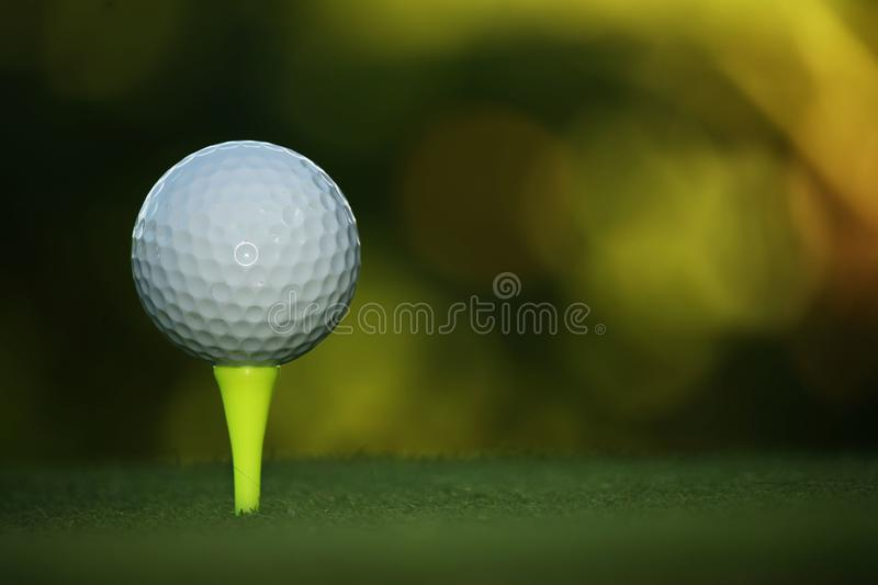 Golf ball on tee in beautiful golf course at sunset stock photos