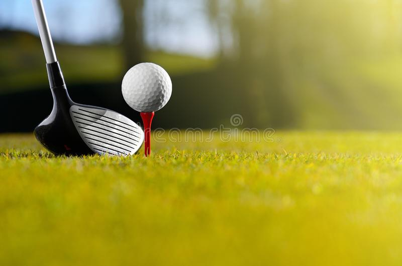 Golf ball on tee with driver. Close up of white golf ball on red tee with driver club on green course with copy space royalty free stock image