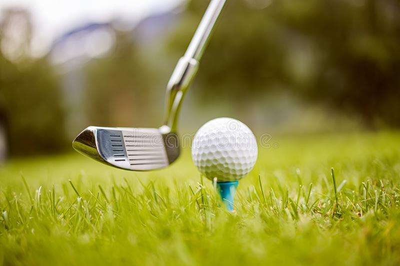 Golf ball on tee in front of driver stock images