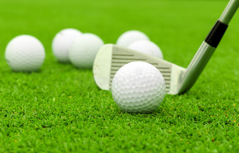 Golf ball on tee in front of driver on green course royalty free stock photos