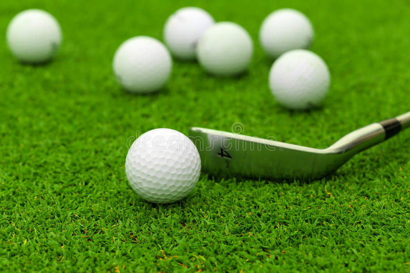 Golf ball on tee in front of driver on green course stock photography