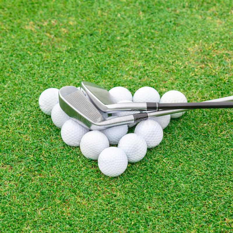 Golf ball on tee in front of driver green course stock photo