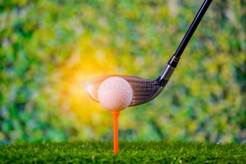 Golf ball on tee and golf club to hitting it stock image