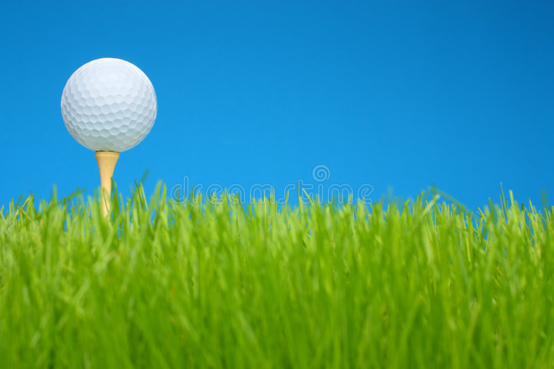 Golf Ball On Tee In A Grass Field Stock Photo