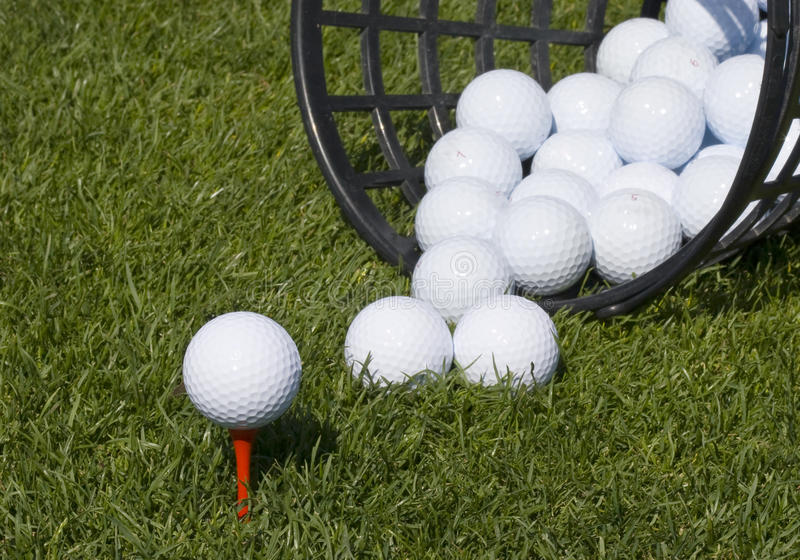 Golf ball teed up. On red tee with basket of range balls tipped over and balls spilling onto grass royalty free stock image