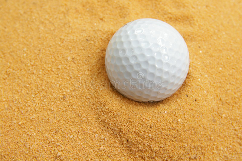 Golf ball in the trap. Closeup of a golf ball in a sand trap stock photos
