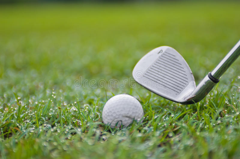 Golf Ball and Wedge. On the Rough Grass royalty free stock photos