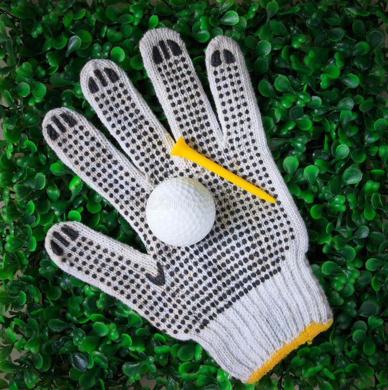Golf ball and yellow tee on hand gloves stock photo