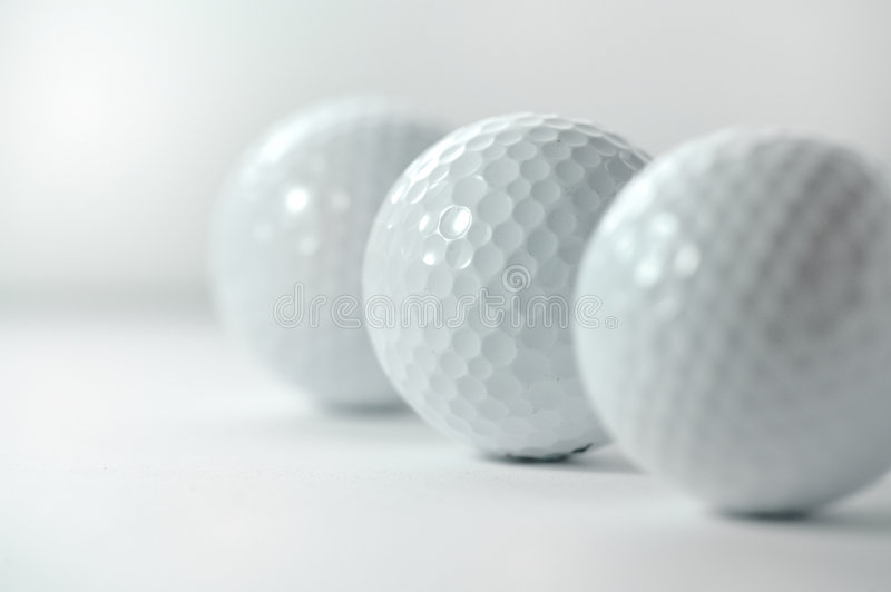 Golf balls. An image of golf balls lined up in a linear manner