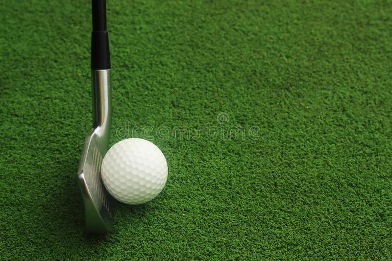 Golf balls and golf clubs on green grass. royalty free stock images