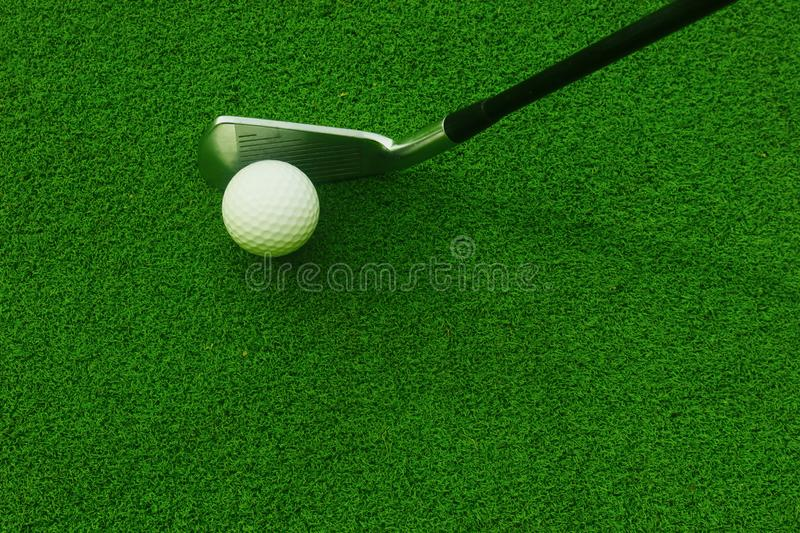 Golf balls and golf clubs on green grass. stock image