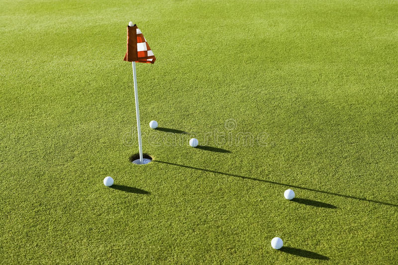 Golf Balls By Flag On Course. View of several golf balls by flag on golf course stock photo