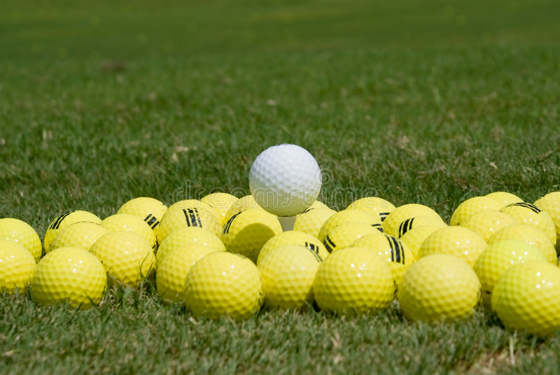 Golf Balls (Medaphore). Yellow Golf Ball at at driving range. White ball set on tee above the rest. Medaphore - Standing Out in a Croud stock photos