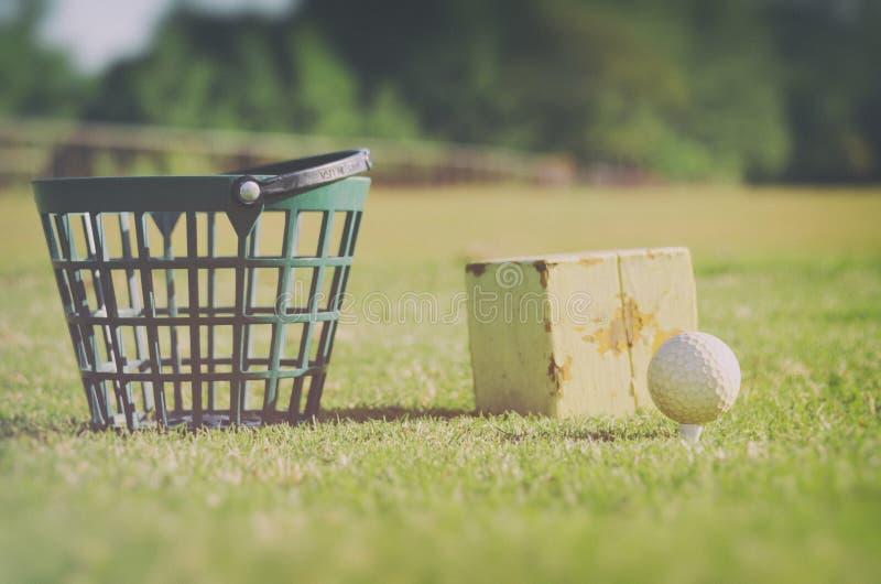 Golf bij de drijfwaaiermand met golfballen bij de ruwe streek natuurlijk stock foto