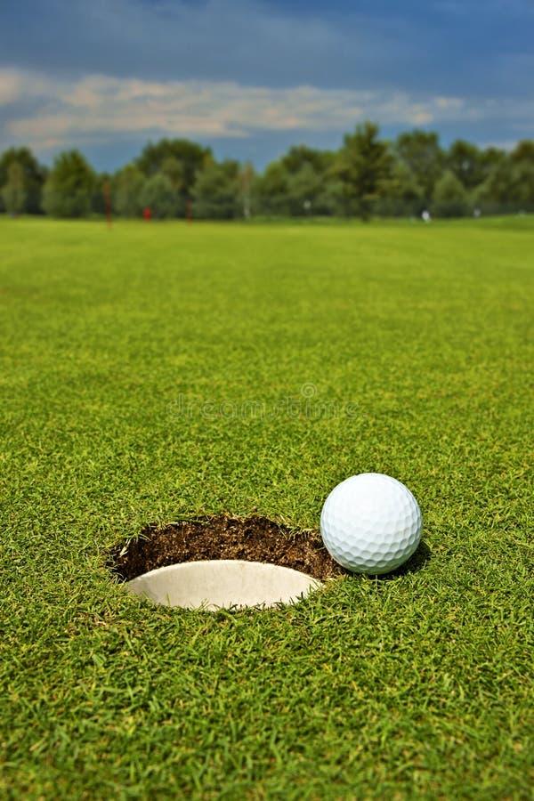Golf boll som ligger på gräsplanen bredvid hålet royaltyfria bilder