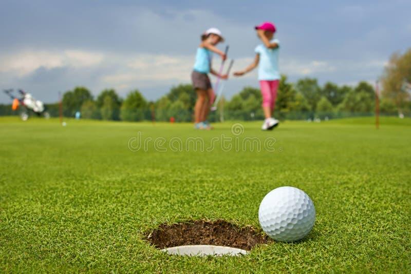 Golf boll som ligger på gräsplanen bredvid hålet, i de två unga golfarna royaltyfri foto