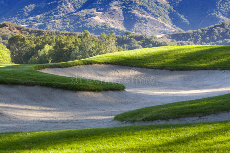 Golf Bunkers. Surrounded by lush green grass and mountains in background royalty free stock images