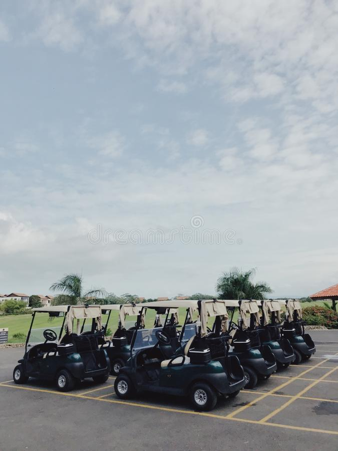 Golf cars on car parking of Altos de Chavon under blue sky with small clouds. Photo of golf club car parking of Altos de Chavon in dominican republic. Parking is stock image