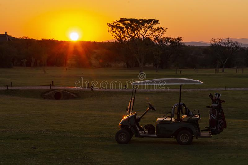 Golf cart on a golf course at dawn and a colorful sunset in the background royalty free stock photo