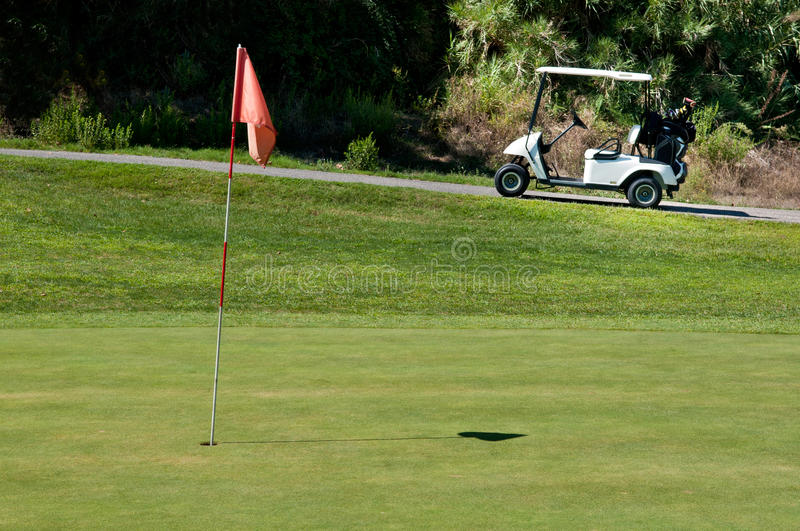 Golf cart next to a hole royalty free stock image