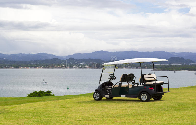 Golf cart. Parked golf cart facing water reservoir with dramatic cloudy sky stock image