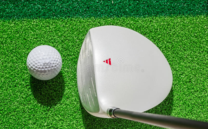 Golf club and golf ball on green grass background. royalty free stock photo