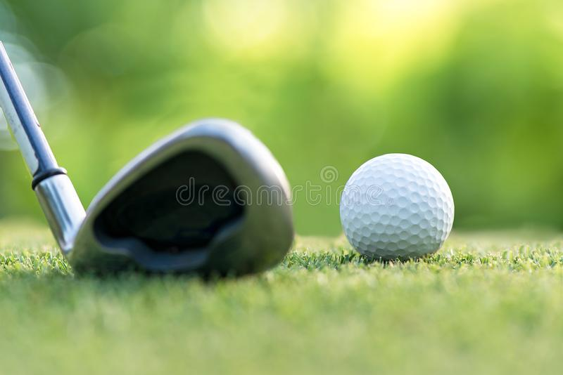 Golf club hitting golf ball along fairway towards green with copy space, green nature background. royalty free stock images