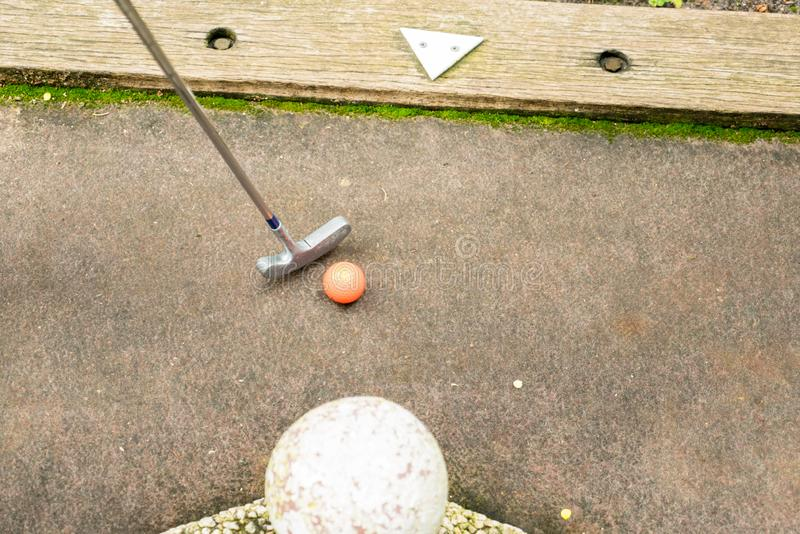 A Golf club and orange ball on a mini golf course with a white marker arrow royalty free stock photo