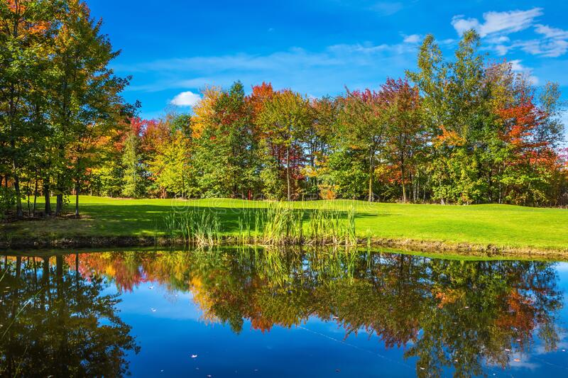 Golf Club on the road to Bromont. French Canada. Concept of Golf tourism. Red, orange and yellow foliage is reflected to clear water of the lake royalty free stock images