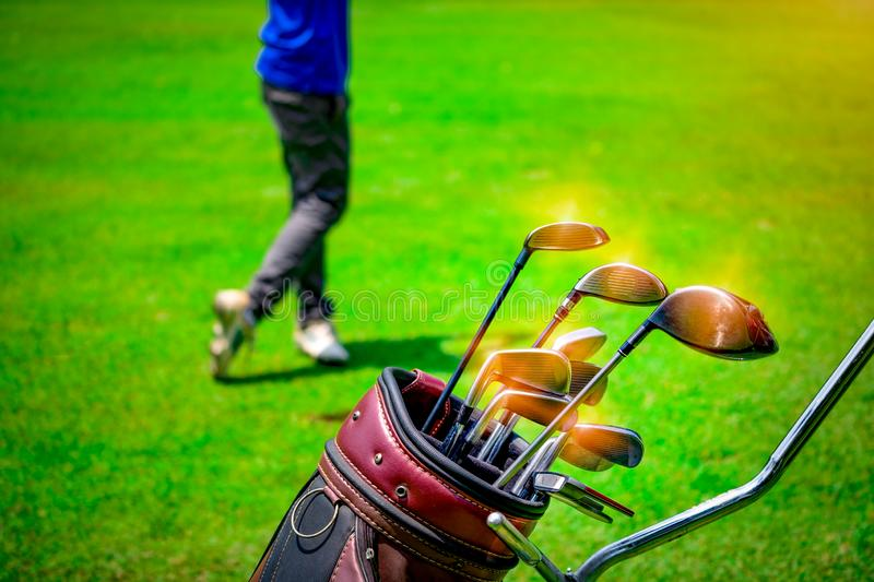 Golf club suit in bag cart and blurred golfer hitting golf ball stock images