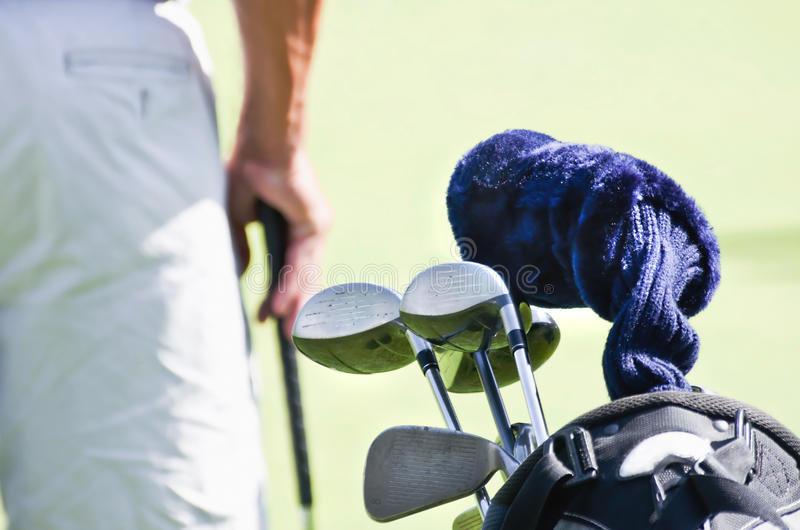 Golfer with golf clubs in bag. A golf player standing on the fairway with a bag of golf clubs stock images