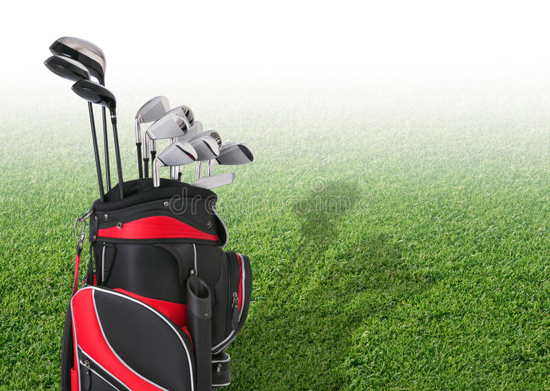 Golf clubs in front of faded tee box grass. Golf clubs in a red and black bag in front of faded tee box grass royalty free stock photo