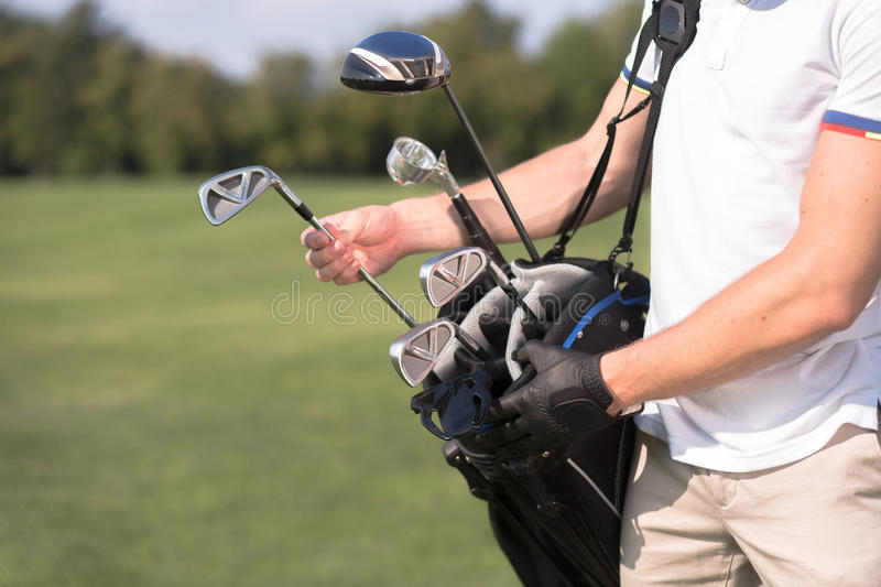 Golf clubs. Golf and golfer concept. Man in white T-shirt removing a golf club from his golf bag to start playing professional golf over green course stock images