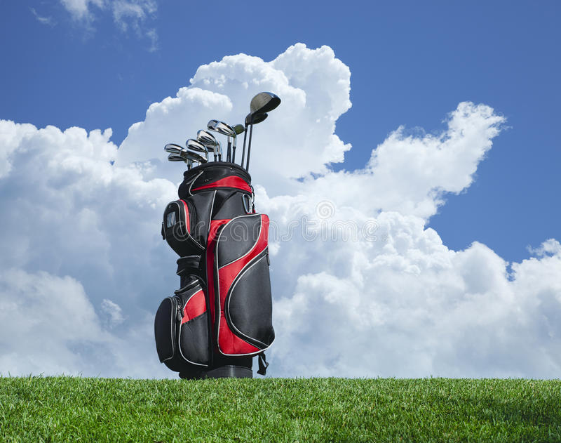 Golf clubs on grass with blue sky and clouds. Golf clubs on grass against a blue sky and clouds stock photos
