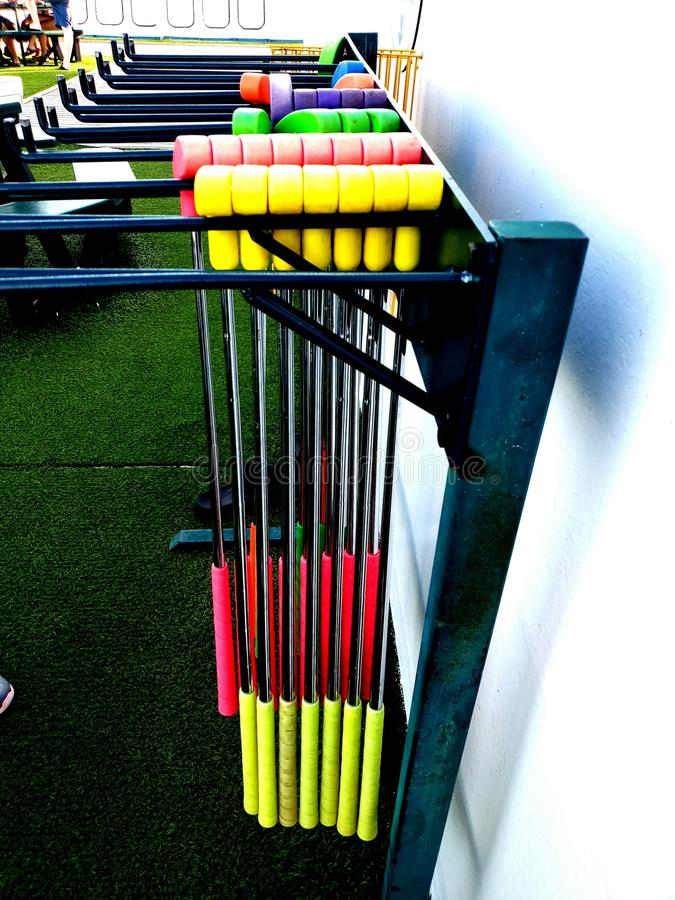 Golf clubs lined up by color and hanging on a mini golf course royalty free stock image
