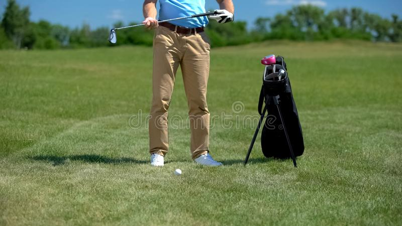 Golf coach holding iron club, preparing to hit ball, sport equipment bag nearby stock photos
