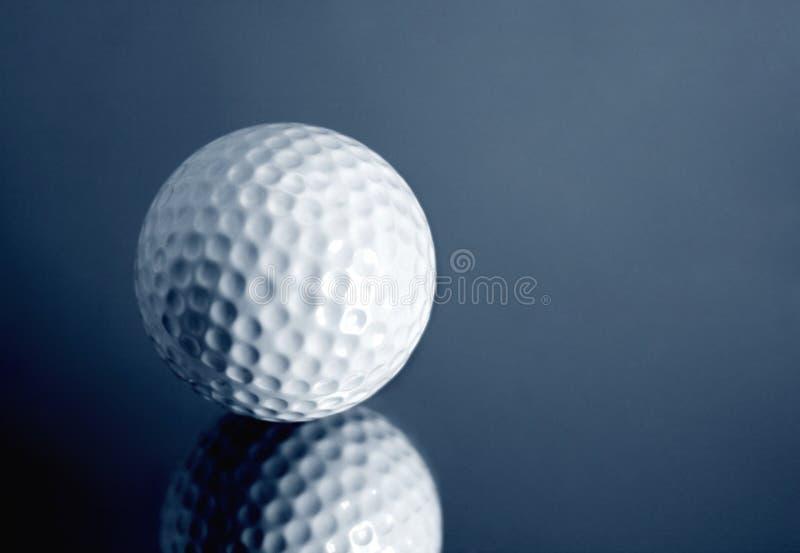 Golf concept. Golf ball on mirror surface (studio shot royalty free stock photo