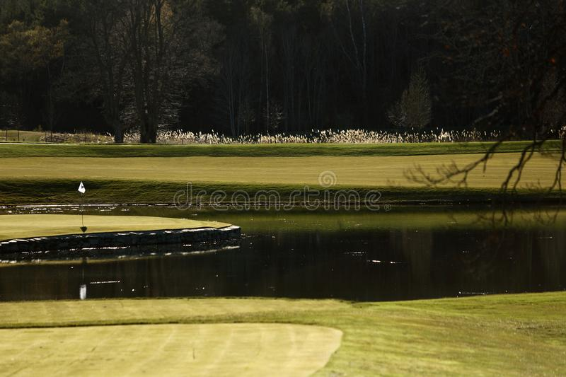 A golf course with roads, bunkers and ponds and with flag. A golf course with bunkers and ponds and with flag stock images