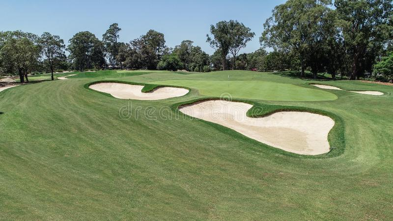 Golf course fairway and green with sand bunker hazards surrounded by trees against blue sky stock photo