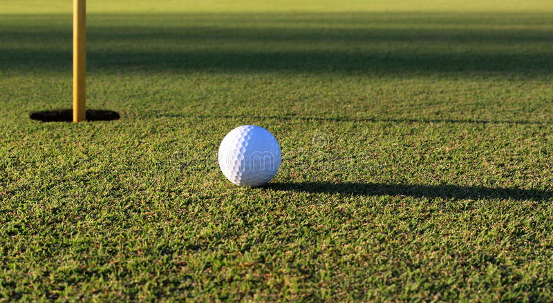 Golf Course Green. Close up of a golf ball on a green next to the cup royalty free stock images