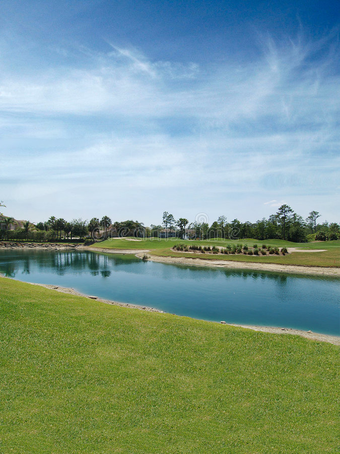Golf Course lake. A Blue lake on a golf course with a bright blue sky royalty free stock photo