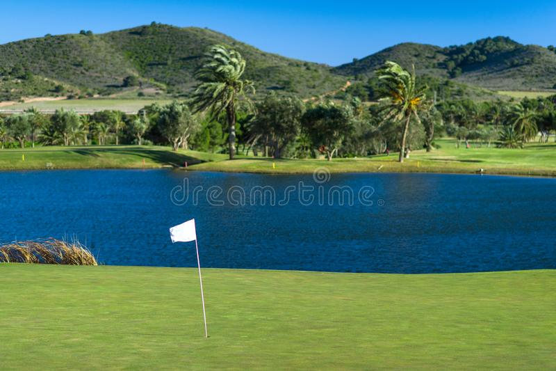 Golf course with palms and hills. A beautiful photo of a golf course with green grass and well shaped hills. The flag flutters in the wind. Photo taken in Spain royalty free stock images