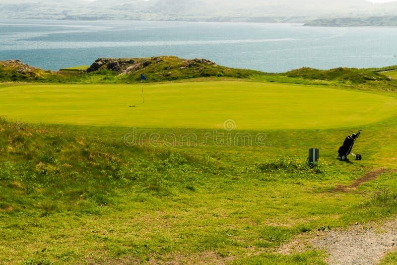 Golf course putting green sea in background and golf bag. Clifftop putting green with bag and sea, Nefyn & District Golf Club, Morfa Nefyn, Llyn Peninsula royalty free stock photos
