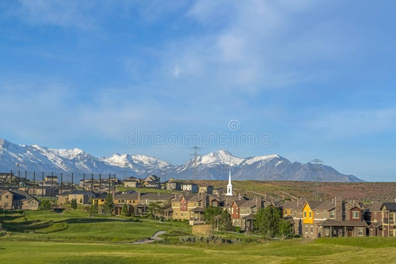 Golf course and residential area with idyllic snowy mountain and blue sky view stock photography